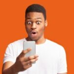 Closeup portrait of surprised african guy looking at phone
