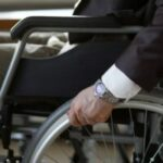 Disability businessman with wheelchair against business office